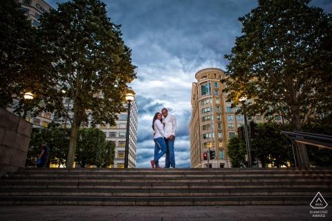 Symmetrisches England vor der Hochzeit Liebesschießen   Engagement-Porträt eines Paares, das an der Spitze der konkreten Treppe steht