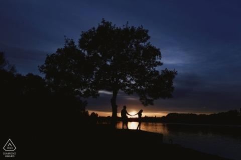 UK Engagement Fotos in der Nacht. Porträt vor der Hochzeit des Händchenhaltens eines Paares als die Sonne stellt ein.