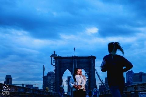 Brooklyn Bridge New York Verlobungsfotograf. Ein Läufer übergibt seine Porträtposition.