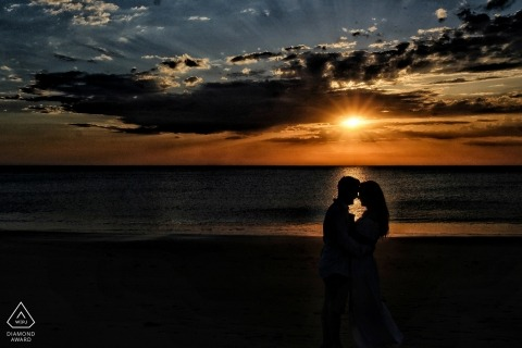 Séance de couple de fiançailles à la plage au coucher du soleil