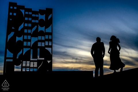 New York City engagement photography | artwork and couple are silhouetted in black against dramatic blue sky