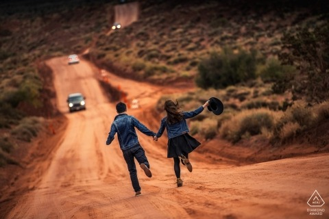 A couple runs down a red dirt road with cars in the desert during an engagement shoot