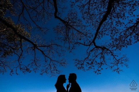 Deep blue sky and a couple silhouetted with the trees - Brazil engagement photography