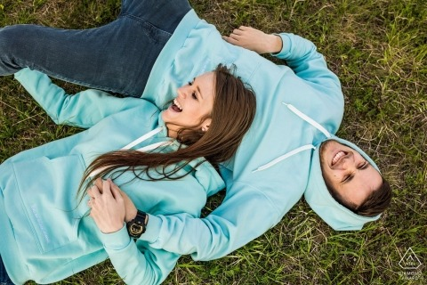 Czech Republic couple lying in the grass with matching sky blue hoodies for their pre-wedding portraits