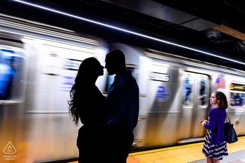 La coppia impegnata posa per il ritratto della siluetta con un'automobile della metropolitana di passaggio