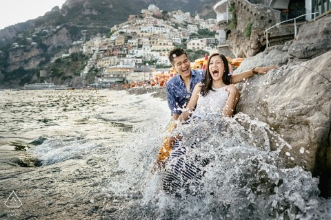 Umbria destination engagement session | pre-wedding portraits with the couple of getting soaked by crashing waves on the rocks