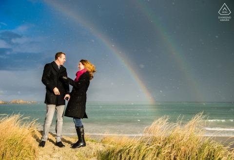 De pre-huwelijksfotograaf van de Kanaaleilanden krijgt geluk met dubbele regenbogen tijdens deze strandfotoshoot