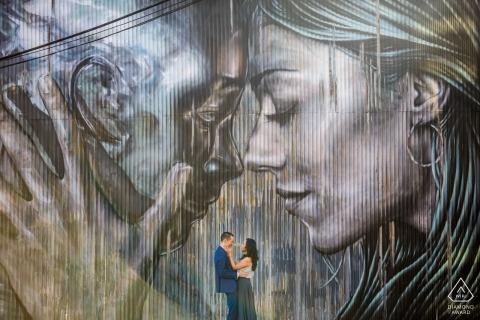 Der in Los Angeles lebende Verlobungsfotograf - ein Paar posiert vor einem großen Wandbild an der Wand hinter ihnen