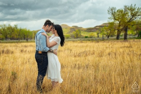 Canadian pre-wedding portraits | Alberta couple stands in a field of dead grass for their engagement session