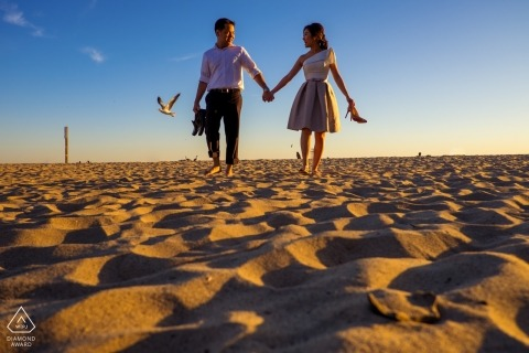Southern California engagement photos at the beach - portrait of a young couple walking hand-in-hand in the sand carrying their shoes as a seagull takes flight behind