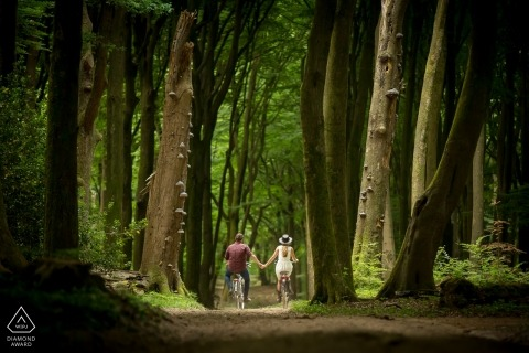 Netherlands prewedding shoot on bikes holding hands on a forest trail