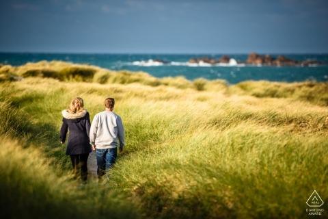 Séance de portrait de couple dans les îles Anglo-Normandes de Guernesey / un couple marchant dans les hautes herbes jusqu'à la plage
