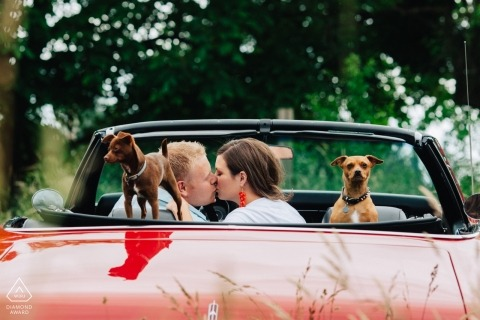 Seattle engagement photographer - the couple kisses in the red convertible car with their two small dogs