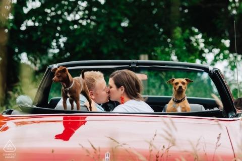 Fotografo di fidanzamento di Seattle - la coppia si bacia in auto convertibile rossa con i loro due cani di piccola taglia