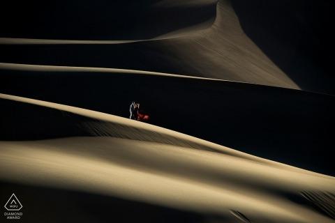 Séance de fiançailles avant les dunes de sable - portrait de couple dans le désert