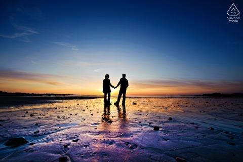 Kanaaleilanden Zonsondergangportret - verlovingsfoto van een paar gesilhouetteerd op het kleurrijke strand