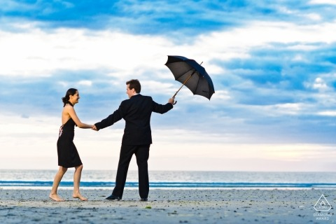 Guernsey formal engagement shoot - Beach portraits while dressed in black with black umbrella