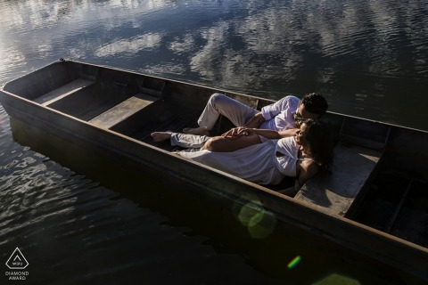 Prewedding portrait of a couple in a boat with reflected clouds | Goias Engagement Photographer