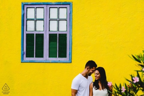 Minas Gerais engagement portrait session with yellow painted wall behind the couple.