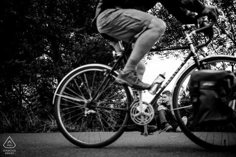 Ritratto in bianco e nero di una coppia di fidanzati seduti sul marciapiede a Seattle mentre un ciclista pedala