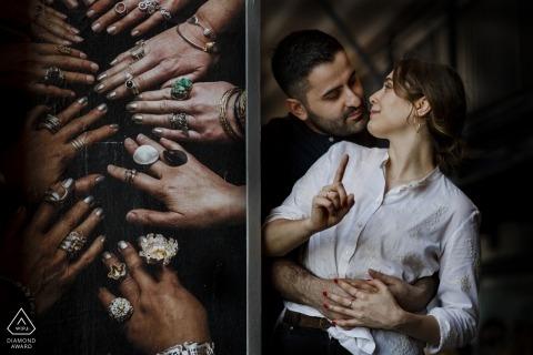 Couple d'Istanbul pose pour leur portrait pré-mariage près d'un panneau de signalisation publicitaire photo avec beaucoup de mains et anneaux
