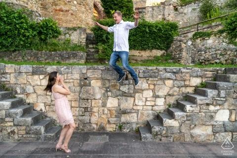 Baden-Württemberg bruid als horloges als haar verloofde springt uit een zeer hoge stenen muur tijdens engagement portret sessie