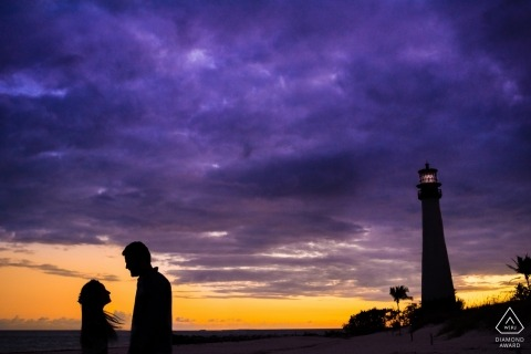 A vibrant purple and yellow sky create a dramatic backdrop for this lighthouse and silhouetted couple for their engagement portrait