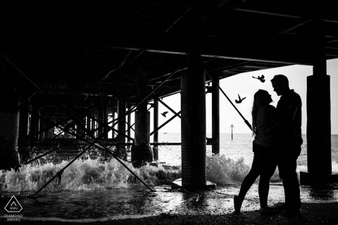 Waves crash against the pier during this silhouetted Full body engagement portrait in Devon UK