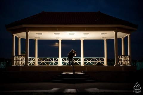 Night time engagement portrait in Boulder CO under a fully lit gazebo