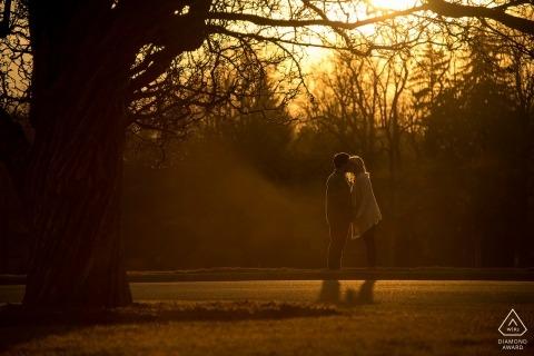 Couple s'embrassant sous un très grand arbre au coucher du soleil à Boulder au Colorado pour leurs portraits de fiançailles