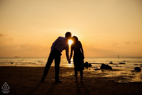 Kissing at the beach during sunset in this San Francisco bay engagement session