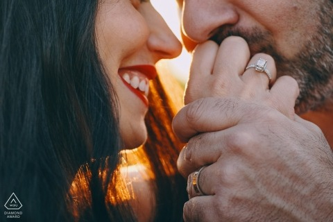 A very tight shot of this Czech Republic couple as he kisses the hand of his fiancée with a ring on it