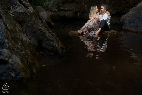 Brazil pre-wedding portrait of couple sitting on a rock in the water
