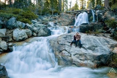 Lake Tahoe couple sits on a rock next to a waterfall with a long slow shutter