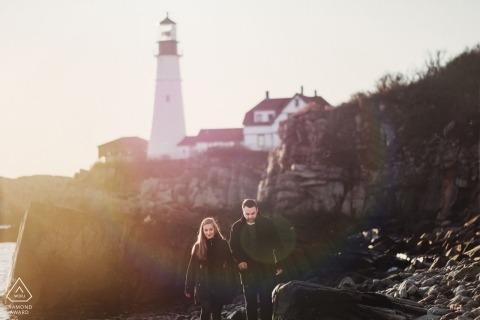 Portland Maine engagement portraits of a couple walking the rocky beach near a lighthouse