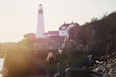 Portland Maine engagement portraits of a couple walking the rocky beach near a lighthouse