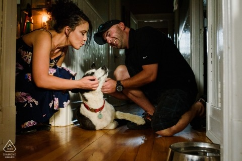 A Montréal couple Play with their dog in their home while their engagement portraits are created