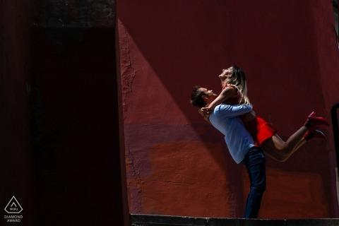 Couple d'Istanbul Jouez au soleil de l'après-midi contre un mur de stuc rouge pour leurs portraits d'avant le mariage