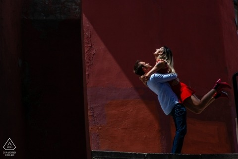 Istanbul couple Play in the afternoon sun against a red stucco wall for their pre-wedding portraits