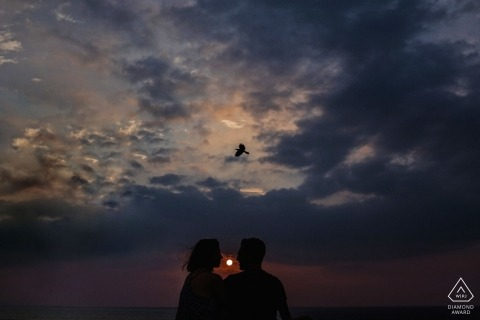A solo bird flies overhead during this sunset engagement session in Sri Lanka