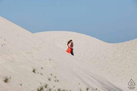 Taking her red dress to the desert sand dunes for an engagement portrait