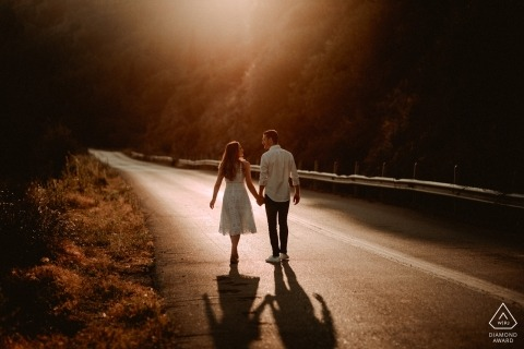 Athens engagement portrait of a couple walking down an empty road toward the setting sun