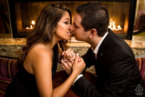 District of Columbia engaged couple kiss by the fireside for their engagement portrait