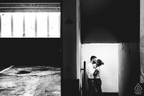 Engaged couple kiss in the stairwell of an abandoned building