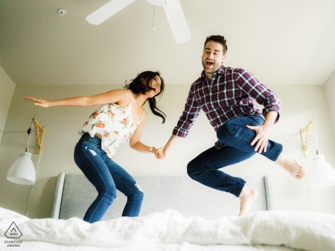 Seattle in-home engagement photography of couple jumping on bed