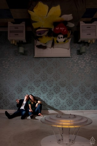 A couple sits on the ceiling in upside down house for their pre-wedding portrait session in Chicago