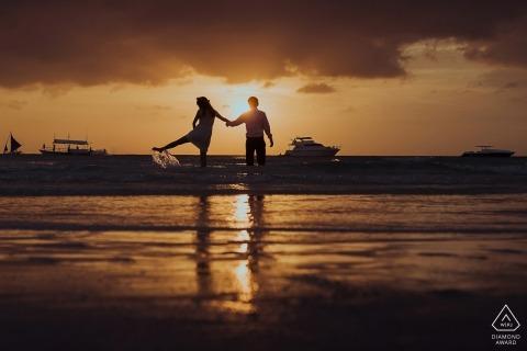 Zhejiang verloofd paar spelen in de ondiepe wateren op het strand tijdens zonsondergang voor hun pre-bruiloft portret