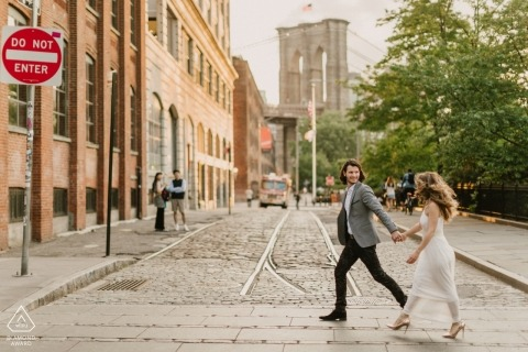 Holding hands and quickly walking across the street during their NYC engagement session