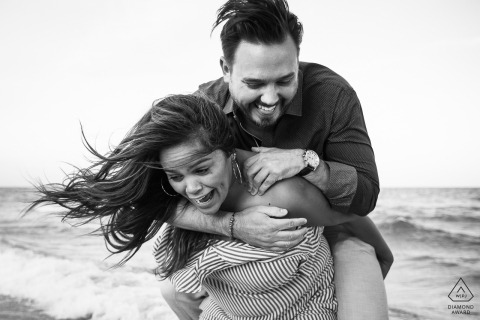 She's taking her fiancé for a piggyback ride at the beach in Miami Florida during their engagement portrait session