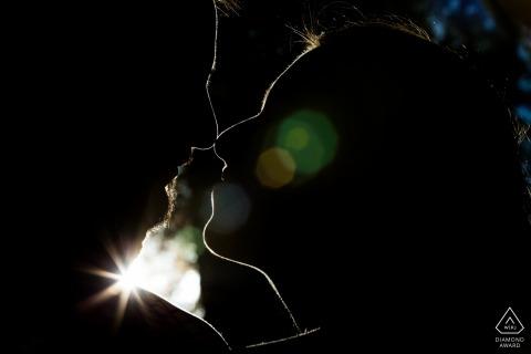 Tiré au soleil avec la lumière de la jante, ce couple a un magnifique portrait de fiançailles silhouette